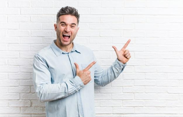Młody przystojny mężczyzna na tle ściany z cegieł, wskazując palcami wskazującymi na przestrzeń kopii, wyrażając podekscytowanie i pożądanie.