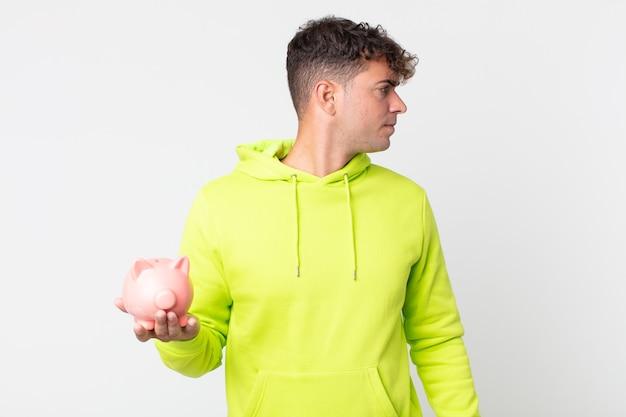 Młody przystojny mężczyzna na widoku profilu myślący, wyobrażający sobie lub marzący i trzymający skarbonkę