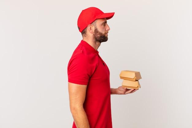 Młody przystojny mężczyzna na widoku profilu myślący, wyobrażający sobie lub marzący o koncepcji dostarczania burgera