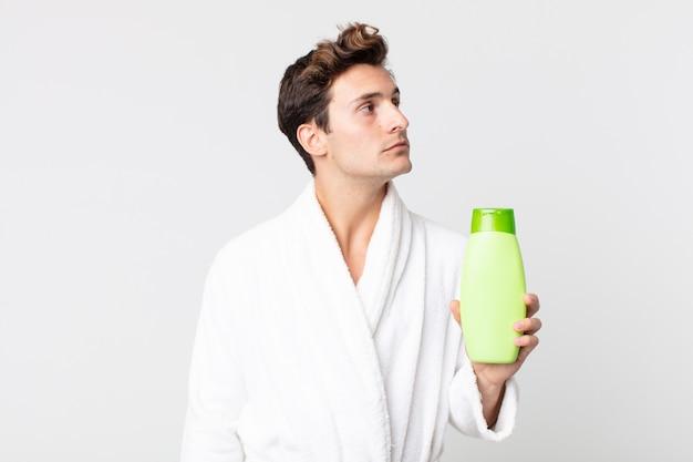 Młody przystojny mężczyzna na widoku profilu myślący, wyobrażający sobie lub marzący ze szlafrokiem i trzymający butelkę szamponu