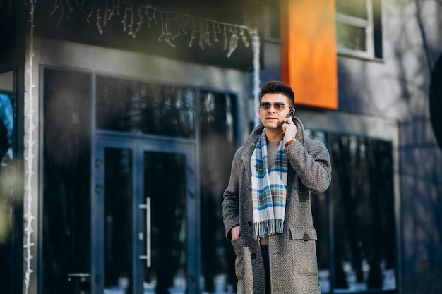 Młody przystojny mężczyzna na zewnątrz za pomocą telefonu