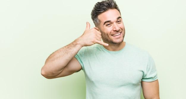 Młody przystojny mężczyzna na zielonym tle przedstawiający gest rozmowy telefonicznej palcami.