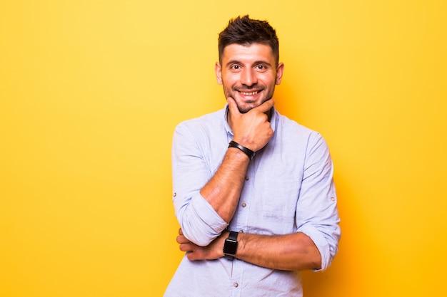 Młody przystojny mężczyzna na żółtym tle na białym tle pewny siebie patrząc w kamerę, uśmiechając się ze skrzyżowanymi rękami i ręką uniesioną na brodzie. myśl pozytywnie.