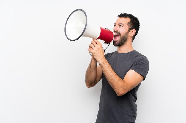 Młody przystojny mężczyzna nad odosobnioną biel ścianą krzyczy przez megafonu