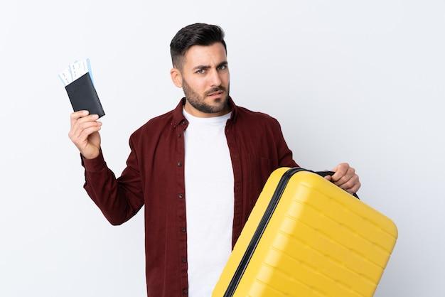 Młody przystojny mężczyzna nad odosobnioną biel ścianą nieszczęśliwą w wakacje z walizką i paszportem