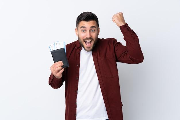 Młody przystojny mężczyzna nad odosobnioną biel ścianą szczęśliwą w wakacje z paszportem i samolotowymi biletami