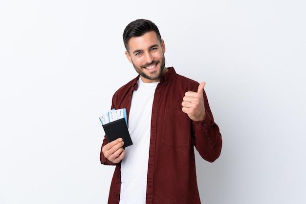 Młody przystojny mężczyzna nad odosobnioną biel ścianą w wakacje trzyma paszport i samolot z kciukiem up