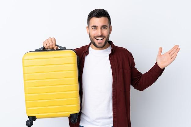 Młody przystojny mężczyzna nad odosobnioną biel ścianą w wakacje z podróży walizką i zaskakujący