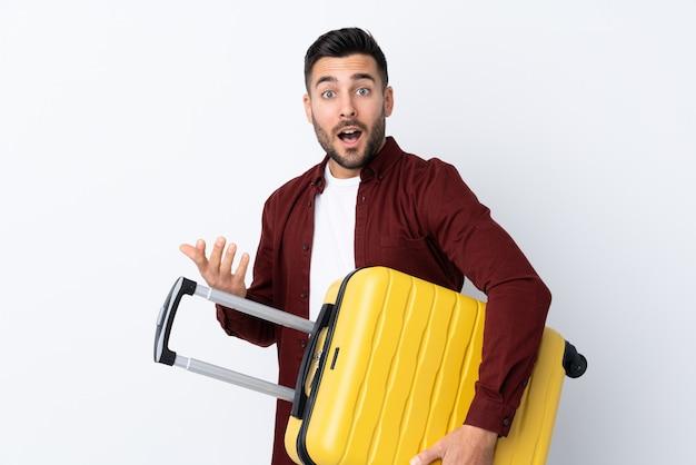 Młody przystojny mężczyzna nad odosobnioną biel ścianą w wakacje z podróży walizką