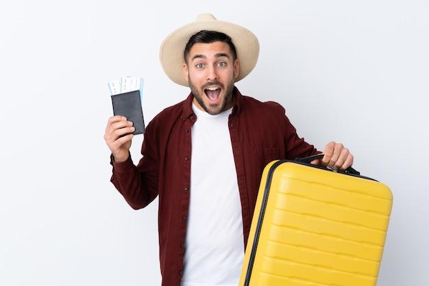 Młody przystojny mężczyzna nad odosobnioną biel ścianą w wakacje z walizką i paszportem i zaskakujący