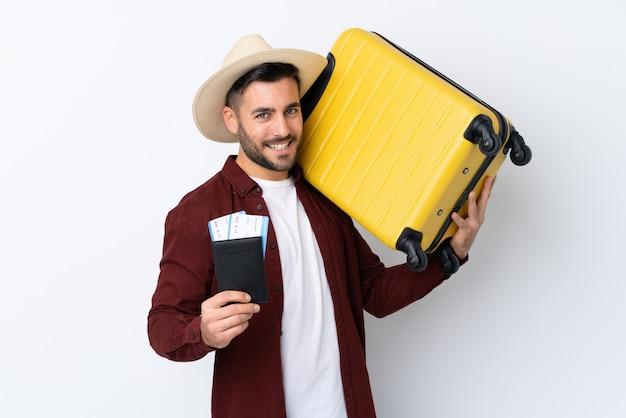 Młody przystojny mężczyzna nad odosobnioną biel ścianą w wakacje z walizką i paszportem