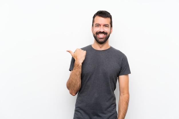 Młody przystojny mężczyzna nad odosobnioną biel ścianą wskazuje z boku przedstawiać produkt