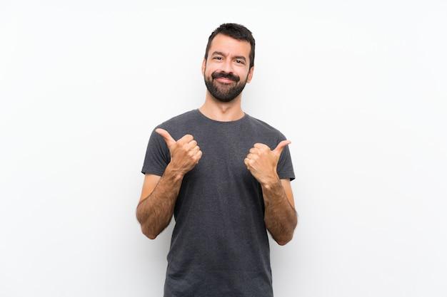 Młody przystojny mężczyzna nad odosobnioną biel ścianą z aprobatami gestykuluje i ono uśmiecha się