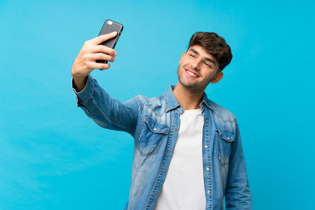 Młody przystojny mężczyzna nad odosobnioną błękit ścianą bierze selfie z wiszącą ozdobą