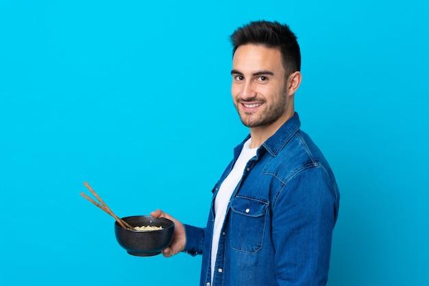 Młody przystojny mężczyzna nad odosobnioną błękit ścianą ono uśmiecha się dużo podczas gdy trzymający puchar kluski z chopsticks
