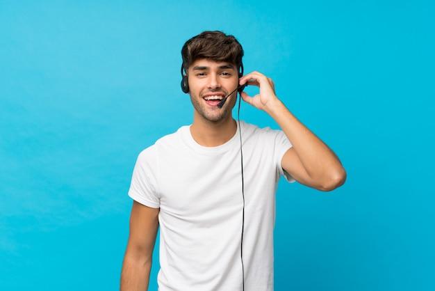 Młody przystojny mężczyzna nad odosobnioną błękit ścianą pracuje z słuchawki