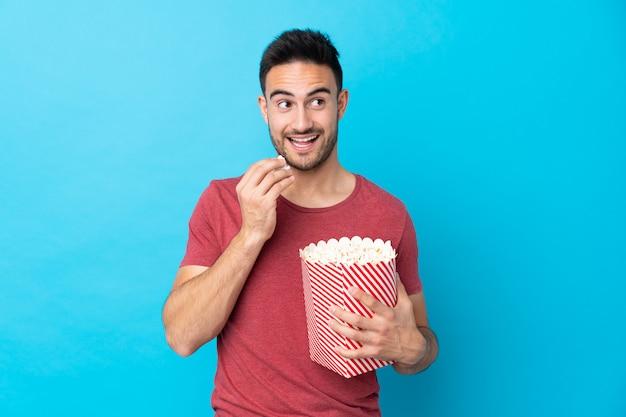 Młody przystojny mężczyzna nad odosobnioną błękit ścianą trzyma dużego wiadro popkorn