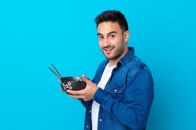Młody przystojny mężczyzna nad odosobnioną błękit ścianą trzyma puchar kluski z pałeczkami