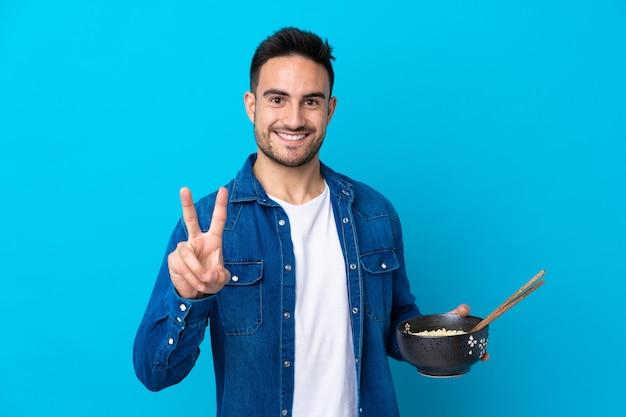 Młody przystojny mężczyzna nad odosobnioną błękit ścianą uśmiecha się znaka zwycięstwo i pokazuje podczas gdy trzymający puchar kluski z chopsticks