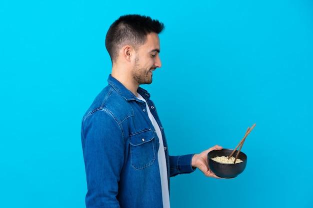 Młody przystojny mężczyzna nad odosobnioną błękit ścianą z szczęśliwym wyrażeniem podczas gdy trzymający puchar kluski z chopsticks