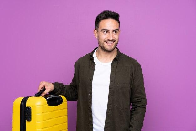Młody przystojny mężczyzna nad odosobnioną purpury ścianą w wakacje z podróży walizką i kapeluszem