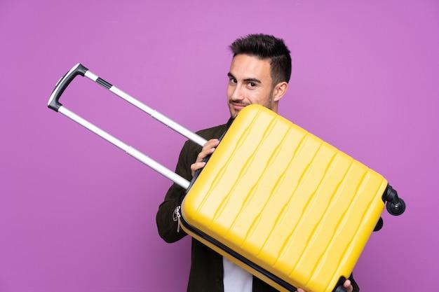 Młody przystojny mężczyzna nad odosobnioną purpury ścianą w wakacje z podróży walizką