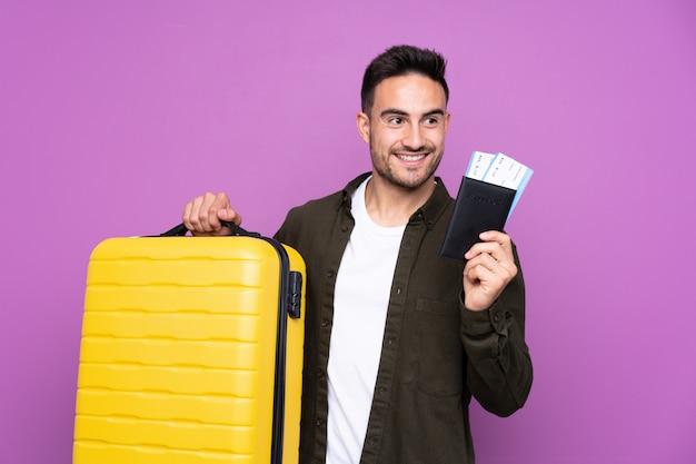 Młody przystojny mężczyzna nad odosobnioną purpury ścianą w wakacje z walizką i paszportem