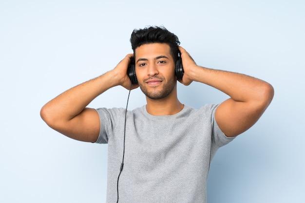 Młody przystojny mężczyzna nad odosobnioną ścianą używać wiszącą ozdobę z hełmofonami