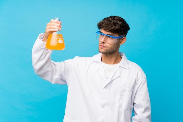 Młody przystojny mężczyzna nad odosobnionym błękitem z naukową próbną tubką