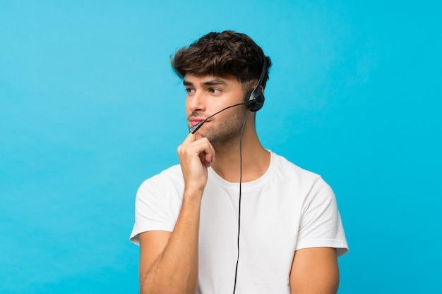Młody przystojny mężczyzna nad odosobnionym błękitnym działaniem z słuchawki