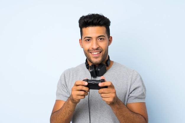 Młody przystojny mężczyzna nad odosobnionym tłem bawić się przy gra wideo
