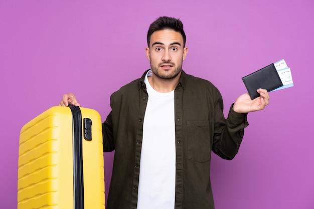 Młody przystojny mężczyzna nad odosobnionymi purpurami izoluje nieszczęśliwego w wakacje z walizką i paszportem