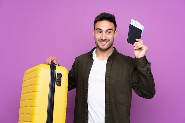 Młody przystojny mężczyzna nad purpurami w wakacje z walizką i paszportem