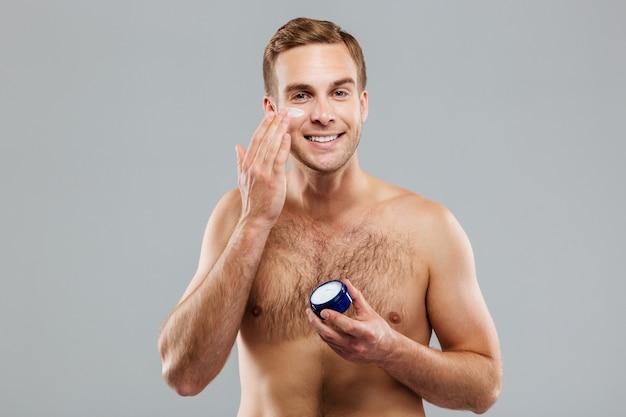 Młody przystojny mężczyzna nakłada kremowy balsam na twarz odizolowaną na szarej ścianie