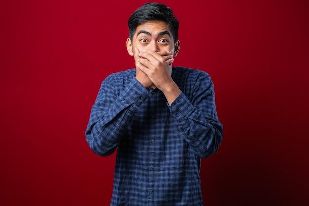Młody przystojny mężczyzna nosi flanelową koszulę na białym tle czerwony zszokowany obejmujące usta rękami za pomyłkę. tajna koncepcja.