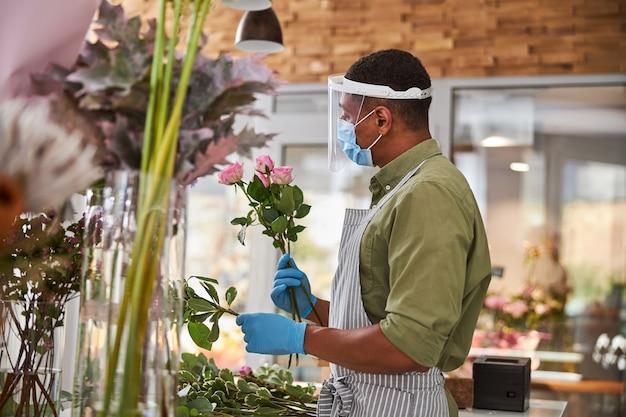 Młody przystojny mężczyzna nosi maskę i bezpieczne szkło podczas robienia bukietów świeżych kwiatów podczas pandemii