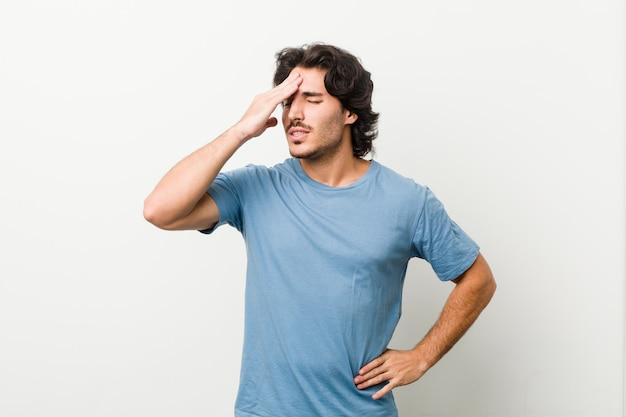 Młody przystojny mężczyzna o białą ścianę, zapominając o czymś, uderzając dłonią w czoło i zamykając oczy.
