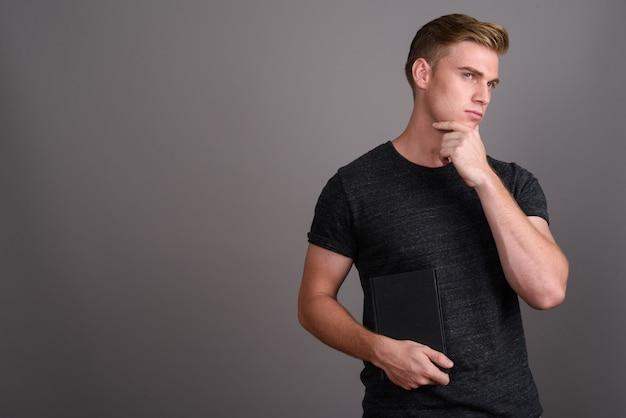 Młody przystojny mężczyzna o blond włosach na sobie szarą koszulę na szarej ścianie