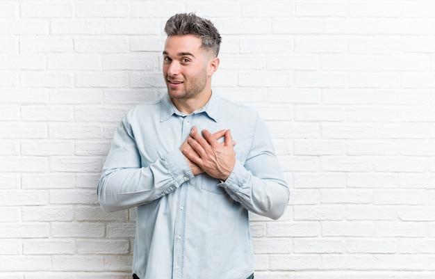 Młody przystojny mężczyzna o ścianę z cegły ma przyjazny wyraz, przyciskając dłoń do klatki piersiowej