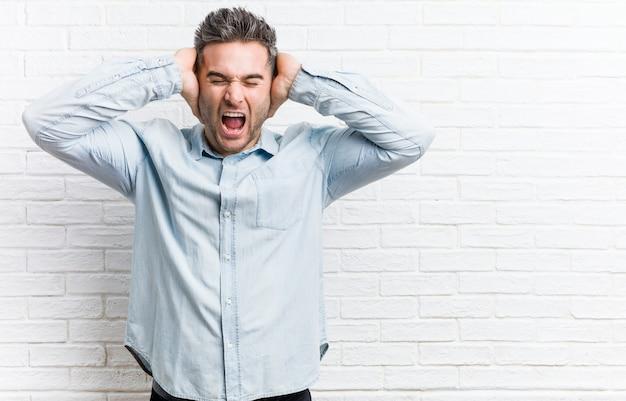 Młody przystojny mężczyzna o ścianę z cegły zakrywającą uszy rękami, starając się nie słyszeć zbyt głośnego dźwięku.