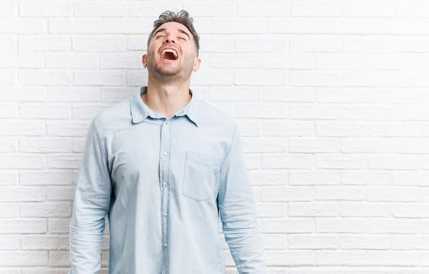 Młody przystojny mężczyzna o ścianę z cegły zrelaksowany i szczęśliwy śmiechu