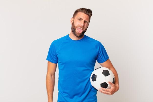 Młody przystojny mężczyzna o wesołej i buntowniczej postawie, żartując i wystawiając język. koncepcja piłki nożnej