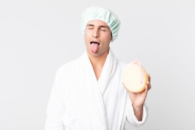 Młody przystojny mężczyzna o wesołej i buntowniczej postawie, żartuje i wystawia język ze szlafrokiem, czepkiem i gąbką