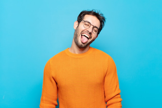 Młody przystojny mężczyzna o wesołym, beztroskim, buntowniczym nastawieniu, żartującym i wystawiającym język, dobrze się bawiąc