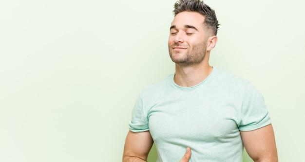 Młody przystojny mężczyzna o zieloną ścianę dotyka brzucha, uśmiecha się delikatnie, jedzenie i koncepcja satysfakcji.