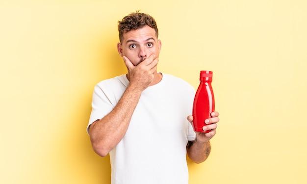 Młody przystojny mężczyzna obejmujący usta rękami z szoku. koncepcja ketchupu