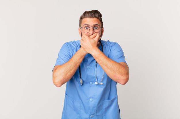 Młody przystojny mężczyzna obejmujący usta rękami z szoku. koncepcja pielęgniarki