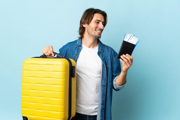 Młody przystojny mężczyzna odizolowywający na niebiesko w wakacje z walizką i paszportem