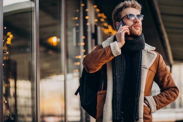 Młody przystojny mężczyzna opowiada na telefonie lotniskiem