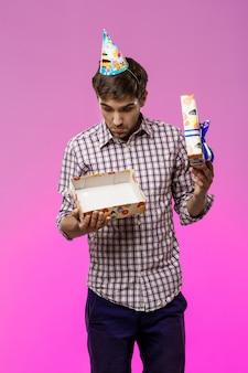 Młody przystojny mężczyzna otwiera prezent urodzinowy nad purpury ścianą.